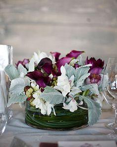 Contemporary Centerpiece Eggplant calla lilies, purple tulips, antique green hydrangeas, dusty miller, geraniums, hypericum berries, and Hawaiian dendrobium orchids