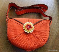 Diese trendy Schultertasche ist aus oranger und dunkelbrauner Wolle gehäkelt und mit einer Lasche und einem großen Knopf zu schließen, die Lasche wird durch eine große 3D-Blume verdeckt.  Sie ist gefüttert, hat 2 kleine Innentaschen und hat lange Henkel(ca. 100cm)