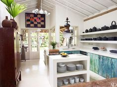 Concrete countertops and shelving complement reclaimed-wood cabinet fronts in the kitchen; the framed artwork is a Ghanaian asafo flag, and the hanging lantern is vintage.