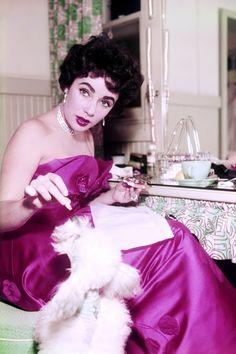 sparklejamesysparkle:  Elizabeth Taylor gives her poodle a treat in her MGM dressing room, 1954.