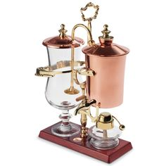 The Genuine Balancing Siphon Coffee Maker. An alcohol burner boils the water inside the copper kettle, causing it to pass through the pipette and into the brewing chamber where it steeps the coffee grounds. As water exits the kettle, the counterweight and hinge elevate the vessel, allowing the spring-loaded candle snuffer to extinguish the burner's flame.