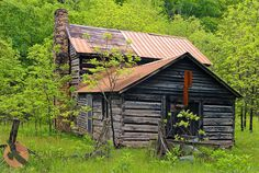 Old chinked log house with stone chimney and tin roof in rural West Virginia.