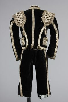 Embroidered rose satin matador cape, late 19th century, couched and embroidered in gold thread and spangled with sequins; together with a black velvet and silver braid matador outfit, comprising blue silk waistcoat, breeches and jacket, Kerry Taylor Auctions Fancy Costumes, Masquerade Ball, Black Velvet, Cape, 19th Century, Braids, Auction, Sequins, Textiles