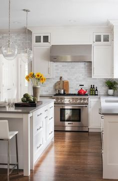 A Thermador range sits against mini calcutta marble subway tiles and between white cabinets donning satin nickel pulls and a light gray quartz countertop.