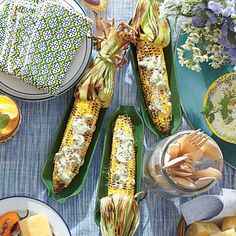 Charred Corn with Garlic-Herb Butter | Use the husks as handles by pulling them back and tying the ends with kitchen string. Soak in cold water at least 10 minutes before grilling to prevent burning. | #Recipes | SouthernLiving.com