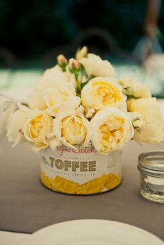 Tightly clustered yellow peonies peek over an antique tin.