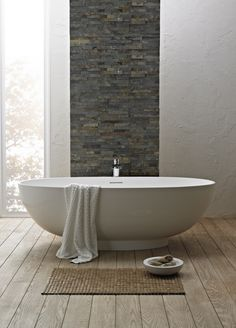 Bathroom. simple bathroom ideas with white acrylic freestanding tub on unfinished hardwood floor combined with natural stone wall panel. Alluring Bathrooms With Freestanding Tubs For Awesome Decoration