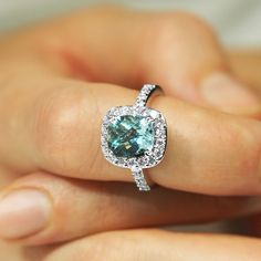A stunning Aquamarine cushion gemstone encircled by the finest round brilliants. Hand crafted in 18 carat white gold with diamond set shoulders. Dress Rings, Jewelry Stores, Heart Ring, Sapphire, Cushion, Jewelry Design, White Gold, Gemstones, Jewellery