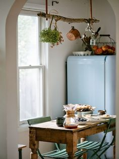 """The kitchen conjures a French farmhouse vibe, thanks to a charming wooden table from Euro Treasures in Salt Lake City. It mingles well with a set of bistro chairs Jana snagged on Craigslist. The powder blue Smeg fridge is another Craigslist find—and at less than $400, a total steal. """"We'll keep it forever,"""" Jana says."""