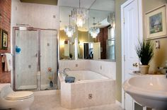 Master bathroom in downtown condo. Includes marble floors, rain shower, sink, linen closet and an oversized jetted tub with a chandelier hanging above. There's even a separate bidet.