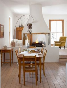 A country style central two-sided fireplace serving as a room divider between the living room and dining room. ©Greg Cox via House and Leisure Decor, House, Interior, Temporary Room Dividers, Home, Adobe House, Home Remodeling, House Interior, Two Sided Fireplace