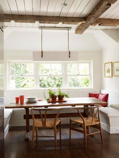 The white bench, walls, and ceiling paired with wood details and pops of red creates an adorable cottage-chic design. Large windows fill the space with natural light. Rather than trying to place chairs (which need space to be pulled in and out) on the ends of this table, the banquette was simply extended into a U-shape, creating two more seats around the table. Love the farmhouse look and chairs