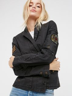 Virginia Grunge Blazer | Military-inspired structured blazer features patch detailing on the sides and a sparkly skull pin on the lapel. Front hip pockets and rugged distressed trim throughout for an authentic look. Hidden button closures down the front.