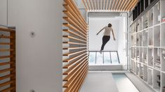 An atrium ringed with wooden slats and topped with trapeze netting is the focal point of this slender dwelling in Montreal, overhauled by Robitaille Curtis.