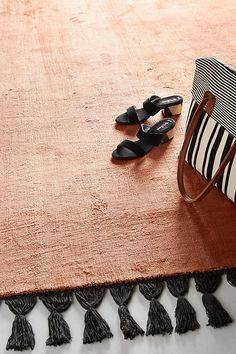 Cozy Rugs to Invest In Before Winter: Burnt orange rug with black tassel trim