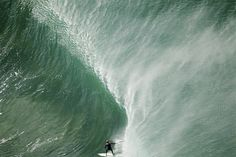 Birdseye view of a surfer riding a big wave, by Ted Grambeau