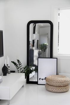 b/w #Skandinavian #living room | love the layering of the black framed mirror & the framed poster