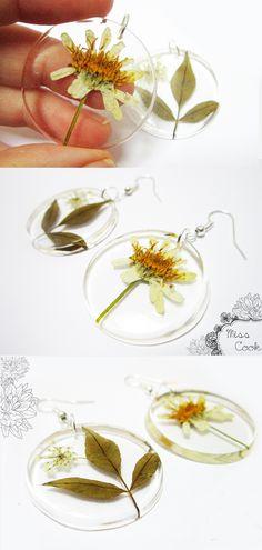 Boucles d'oreilles rondes sous forme de disques plats et transparent, avec inclusion de feuilles et fleurs séchées.  Largeur d'un disque 3,5cm  Support de boucles crochets plaqués argent.  Chaque pièce est unique.