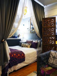 """Natasha's Well-Traveled Brooklyn Studio Apartment - """"Natasha cleverly created a distinct bed nook with the use of curtains and shelving at the food of the bed -"""