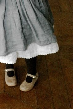 Children girls fashion. Grey smock with white broderie anglais petticoat, dark tights and tan Mary-Jane's.