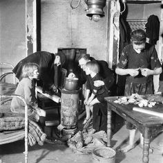 Hunger Winter 1944 - 1945. Dutch family in Amsterdam sitting around a stove while woman cuts up sugar beets. More than 20,000 people lost their lives in Amsterdam and the Western part of the Netherland during the winter of 1944-1945. #amsterdam #worldwar2