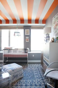A modern nursery design with a white, gray, and orange color scheme featuring an orange and white striped ceiling –