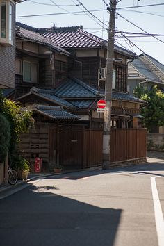 A typical Japanese alley; old house, smooth pavement, rat's nest tangle of electric lines overhead and the overflowing greenery in corners.