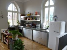 Cucina in muratura con finitura resina satinata e legno laminato finitura acciaio. Mensole in legno laccato. Data: 2011.