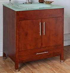 This single sink vanity provides style and functionality for your small or medium bathroom space. The cabinet features a large under sink storage area and a single wide drawer. The medium walnut tone lightens the space while an integrated tempered glass sink and counter top bring a modern tone to the room.