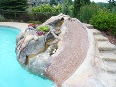 Custom water slide, with rocks complemented by the landscaping inside the concrete rocks!