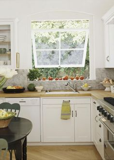 SUNNY KITCHEN  An awning-style window over the kitchen sink opens to 90-degrees, allowing in plenty of natural light and cool breezes. White cabinets, butcher-block counters, and a honed marble backsplash bring classic design elements to a small kitchen.