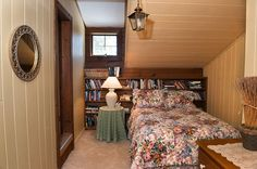 Second floor bedroom in former carriage house with bookshelves used as a headboard.