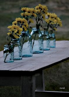 blue mason jars with yellow flowers grace this white farmhouse table