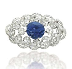 AN ART DECO SAPPHIRE AND DIAMOND BROOCH, BY MISSIAGLIA. Centering upon an oval-shaped sapphire to the circular-cut diamond shoulders, in a baguette and circular-cut diamond oval-shaped frame with scrolls, mounted in platinum, 1930s, 7.5 cm. Signed Missiaglia