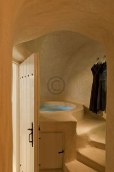 Cob bathing room cave --- idea, rocket stove directly warming tub from outside wall, have no stairs, just be tall enough to sit and have a seat in tub and a deeper soaking area that you can stretch out in... (depends if want to save water in design). Add skylight and have plants like its own little greenhouse.