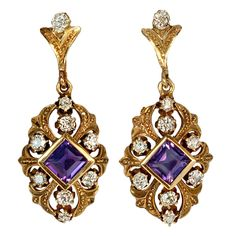 These gold openwork pendant earrings with lily motif are handcrafted in 18K (750) gold, set with two step cut amethysts and eighteen old cut diamonds (over 1 ct tw). Russia, circa 1910