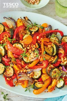 Sweet peppers, courgettes and red onions are roasted together in this colourful veggie salad packed with flavour. Tossed in fragrant garlic and oregano and scattered with pine nuts, this vibrant salad makes a healthy side to a barbecue buffet. | Tesco