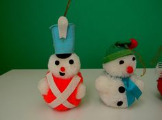 Vintage Set of Three Pom Pom Christmas Ornaments These vintage ornaments are made of yarn and felt and each stand approximately 4 to 4.5 tall. They are in good vintage condition except for a spot or two of yellow glue that is evident where the little felt details were glued on.