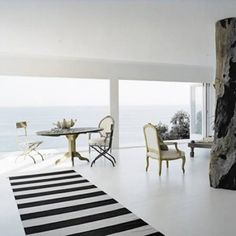 Resin Floor Ocean View Open Plan White Themed Room With Structural Support Disguised As A Tree