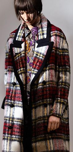 The Check Coat from Burberry, in an oversize cut with striking black wool trim and buttons, worn over a bright floral metallic jacquard shirt dress