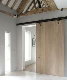New natural wood sliding interior barn door in a restored English barn – Mclaren.Excell via Atticmag
