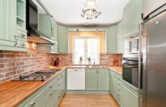 painted kitchen cabinets & brick backsplash - via Sköna hem