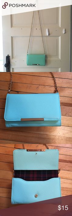 A turquoise cross body wallet from Francesca's A turquoise cross body wallet from Francesca's with a gold chain, flannel material in the inside, many pockets to store cards and money, and a zipper to store coins on the back Francesca's Collections Bags Crossbody Bags