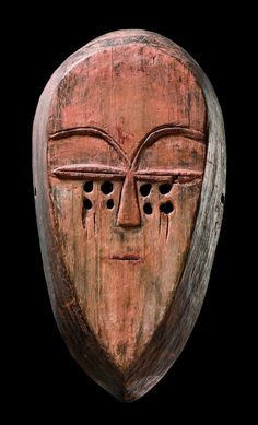 Africa | Mask from the Tsogho people of Gabon | Wood, dark brown patina with traces of red paint and camwood powder || The sculptural style of the Tsogho is similar to that of the Fang, yet the faces of their masks and figures are characterized by a distinct emphasis on the eyebrows which then often form a double semi-circle.