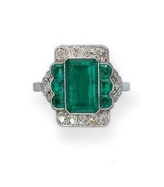 AN ART DECO EMERALD AND DIAMOND RING The rectangular-shaped emerald within old-cut diamond sides and half-moon emerald and diamond openwork shoulders, circa 1925