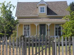 yellow house, cedar color roof. Nice accent of green on door.
