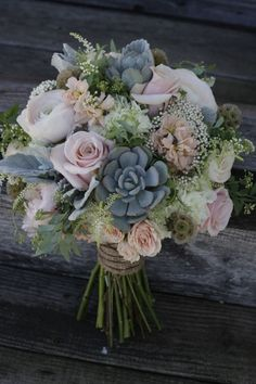 A shabby chic bouquet featuring succulents, dusty pink roses and peonies