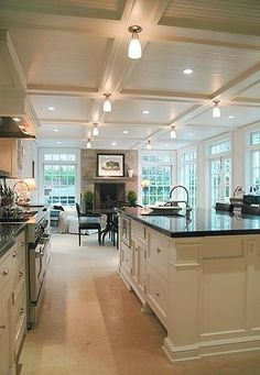 coffered ceiling with beadboard insert wall of windows white cabinetry black granite countertops pale floor historic lighting gooseneck faucet