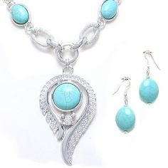 This beautiful set is made of silvertone metal and features an extra large feather shaped pendant embellished with a genuine reconstituted* turquoise stone and sparkling clear crystal. Extra large sized pendant is 3 1/2 inches tall and necklace measures 21 inches in length with a 3 inch extender. Matching earrings feature wire hooks for pierced ears and are 2 inches long. Your set will come to you tucked inside a beautiful velvet pouch complete w...