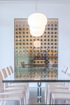 The long glass dining table in this home in Miami's Coconut Grove made by Luminaire.